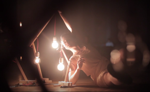 A dancer crouched next to three lightbulbs, expressing one of the five stages of grief