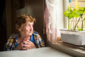 an elderly woman looking out the window experiencing loneliness