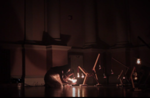 A dancer crouches next to three lightbulbs on the ground and creates shadows behind her, expressing one of the five stages of grief