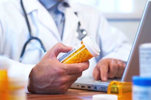 Doctor holding a bottle of opioids for patient