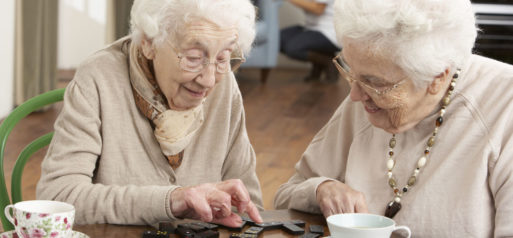 Two elderly women playing scrabble to beat loneliness