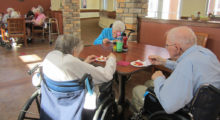 Three nursing home patients sit at a table and enjoy a meal