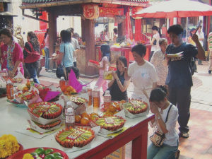 A group of people stand around a table filled with food and incense as part of a Chinese death ritual
