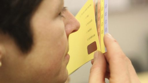 A woman smells a scratch and sniff card that is used in the odor test to detect Alzheimer's and Parkinson's