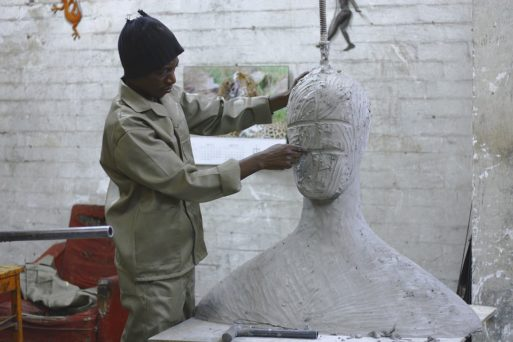 A man uses his creativity to mold a clay sculpture of a giant person on the table of an art workshop