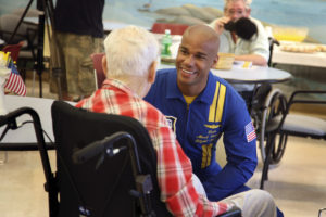 A man in a nursing home sits in a wheelchair and speaks with a member of the US Navy