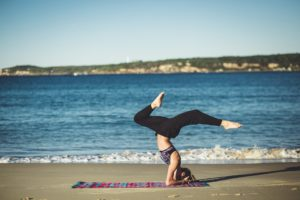 Woman practicing yoga on a beach uses integrative therapies