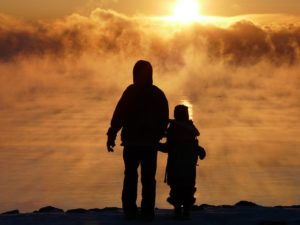 a child and adult in silhouette looking at sky thinking about their own death