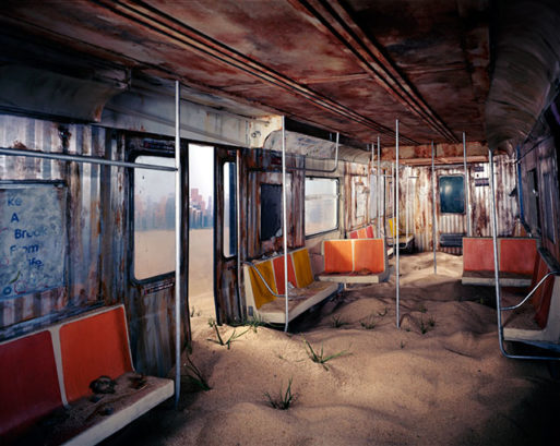 a deserted subway car filled with sand and debris