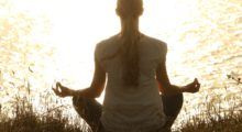 Woman meditating near lake symbolizing cancer therapy