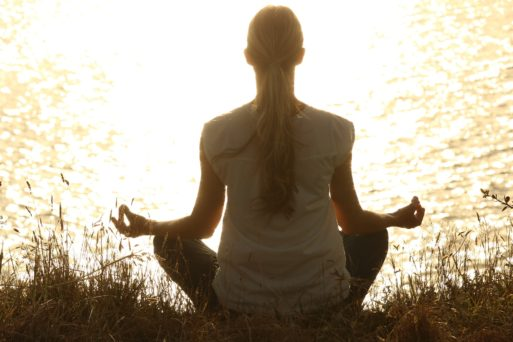 Woman meditating near lake part of integrative therapies