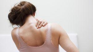 Woman rubbing a sore shoulder should take aspirin