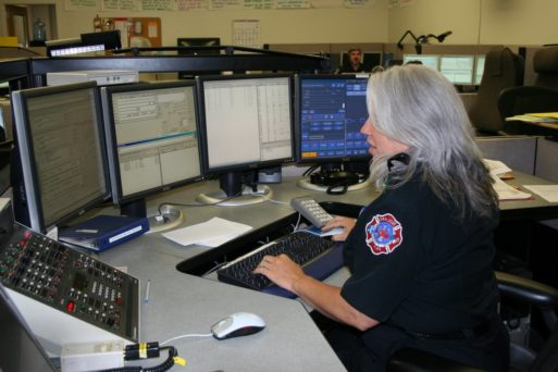 911 dispatcher looking at multiple screens