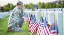 A soldier kneels at the graves of fallen comrades