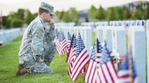 A soldier kneels at the graves of fallen comrades Like Father Like Son