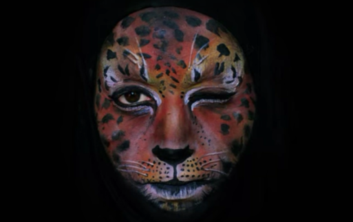 Emma Allen winking and wearing orange face paint that looks like a jaguar's face in her movie about the circle of life