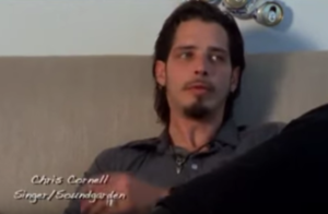 A screenshot of Chris Cornell sitting on a couch talking about Andrew Wood for the documentary