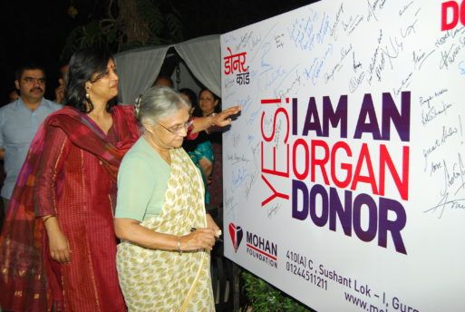 One elderly woman and one middle-aged woman stand next to a sign that says yes I am an organ donor