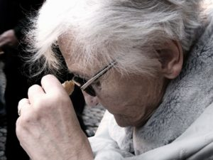 Elderly woman staring down to symbolize dementia