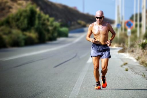 Older man running along a road symbolizing physical activity