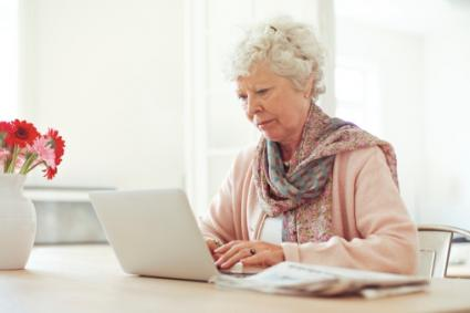 An elderly woman at her laptop could be a victim of elder abuse