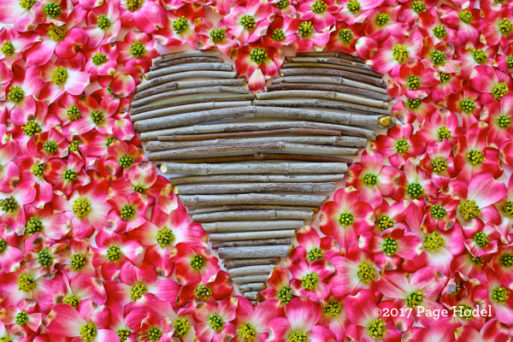 Handamde heart made of twigs surrounded by pink and white flowers
