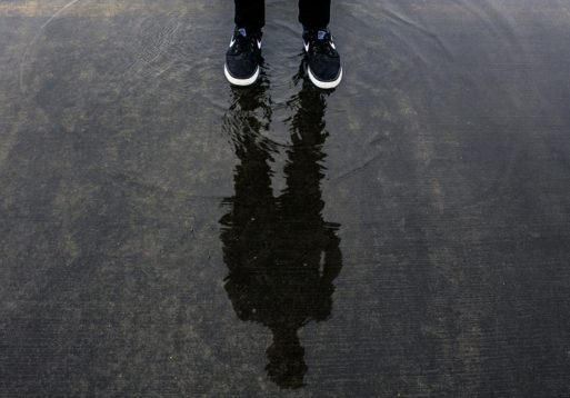 A man standing in a pool of water that shows his shadow and reflection