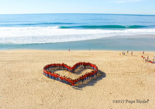 People gathered on the beach in the form of a heart