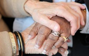 Two pairs of hands represent comfort for victims of elder abuse