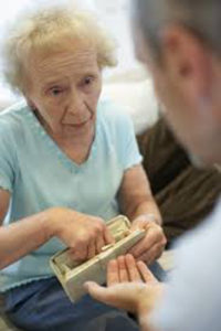An elderly woman giving money to someone with their hand out may be a victim of elder abuse
