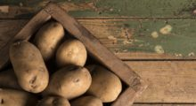 Uncooked potatoes inside of a brown wooden box