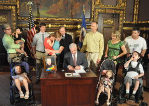 Surrounded by parents and children in wheelchairs, a governor signs a law designed to raise awareness of mitochondrial disease