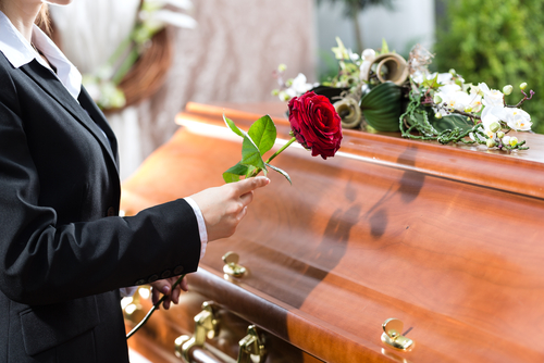 Someone holds a rose up to a coffin as part of a memorial for medical cadavers