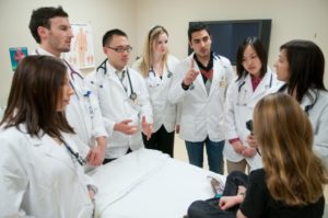 Medical students gathered around a patient discussing medical issues
