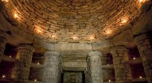 The interior of Willow Row Barrow, featuring a round, high stone ceiling with candles placed throughout the building