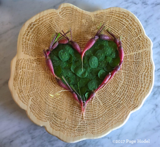 handmade heart made of tiny purple carrots inside a basket