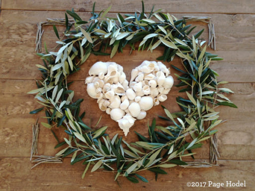 Heart made of seashells surrounded by a circle of leaves