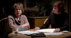 """Two women investigating Sister Cathy's death on """"The Keepers"""" sit at a table together looking at paperwork related to the case"""