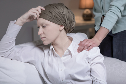 Female cancer patient in a head scarf looking stressed because of her illness
