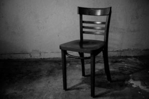 "A single, lonely chair symbolizes ""Empty Chairs at Empty Tables"""