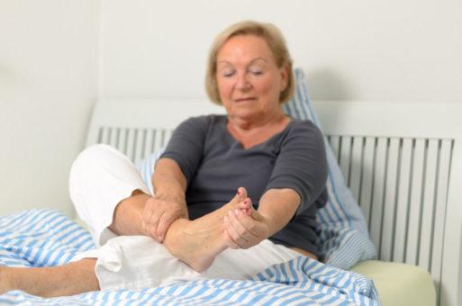 Woman rubbing feet with neuropathy