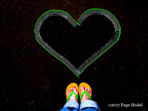 Heart made of nails on black background with sandaled feet