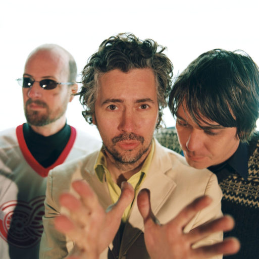 "Portrait of The Flaming Lips with Wayne Coyne, who wrote ""Do You Realize??,"" at the front with hands pointing towards the camera"