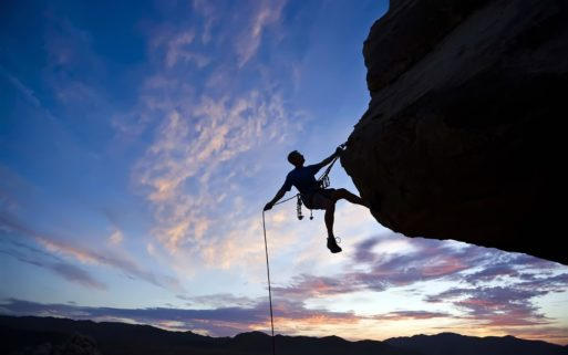 Person rock climbing against a blue sky displaying courage