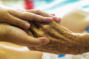 A palliative care nurse holds a patient's hand