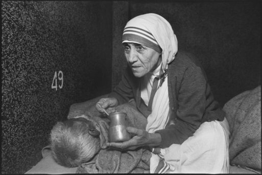 Mother Theresa feeding a sick person in bed
