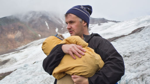 "Phil Elverum, creator of ""A Crow Looked at Me"" holds his baby daughter outdoors in snow"