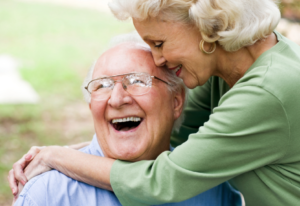 "Woman hugging a happy elderly man saying ""I hope you had the time of your life"""