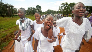 Photo of Liberian children walking and wearing white clothes during a funeral