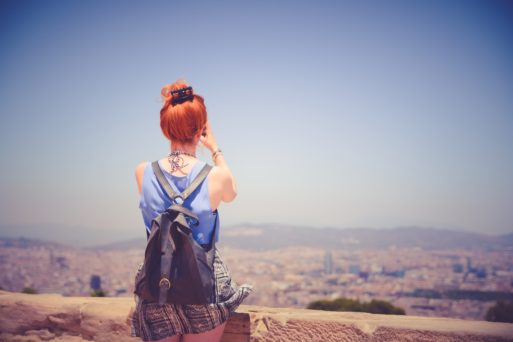 A woman wearing a backpack sits on the edge of a ledge, looking at the city below